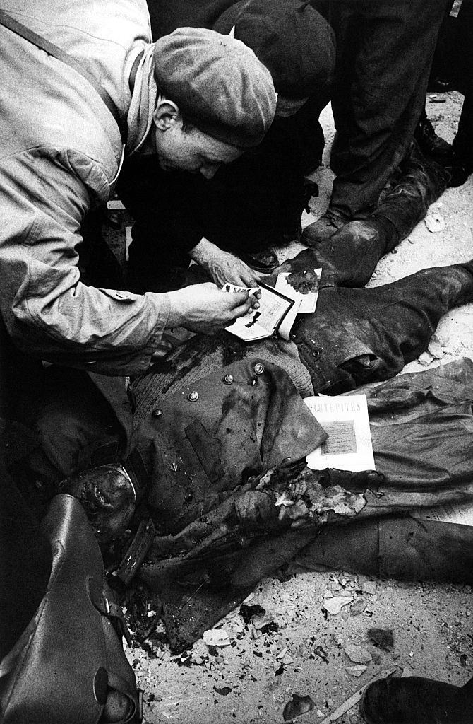 Some insurgents leafing through the documents found on the body of an agent of the Hungarian secret police (AVH). Budapest, November 1956