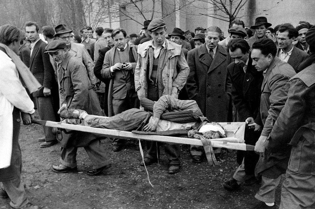 A patriot, wounded during the battle for the headquarters of the Communist Party, is transported on a stretcher to the improvised aid stations. Budapest, November 1956