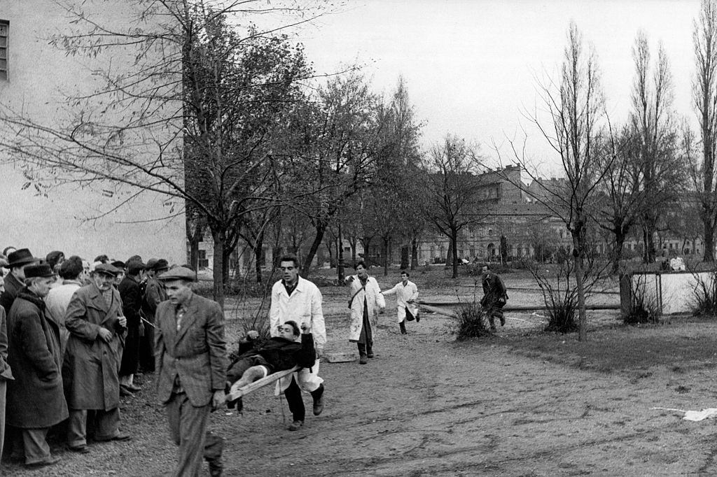 A wounded man is led to safety during the revolt.  Budapest, November 1956