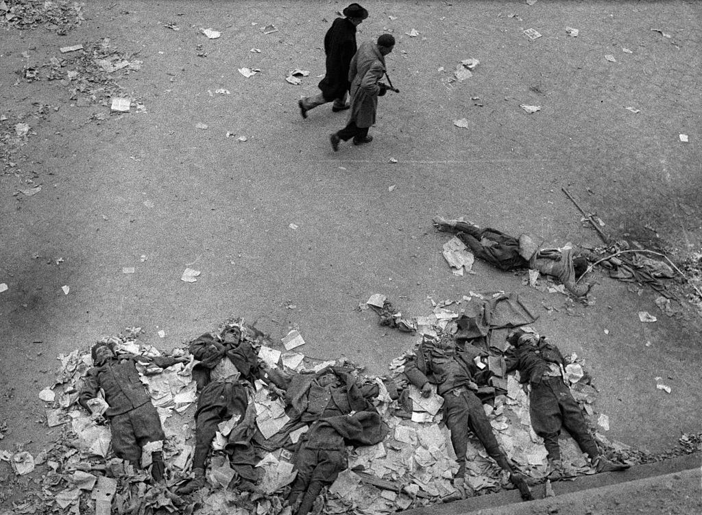 Two Hungarian soldiers walk past the deceased bodies of Soviet secret police during the anti-Communist revolution.