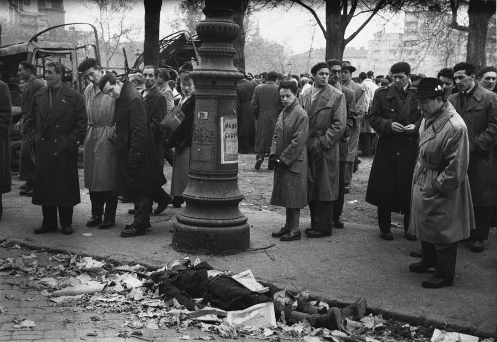 Hungarians stare at the remains of a man from the secret police, the A.V.H. during the 1956 revolution.