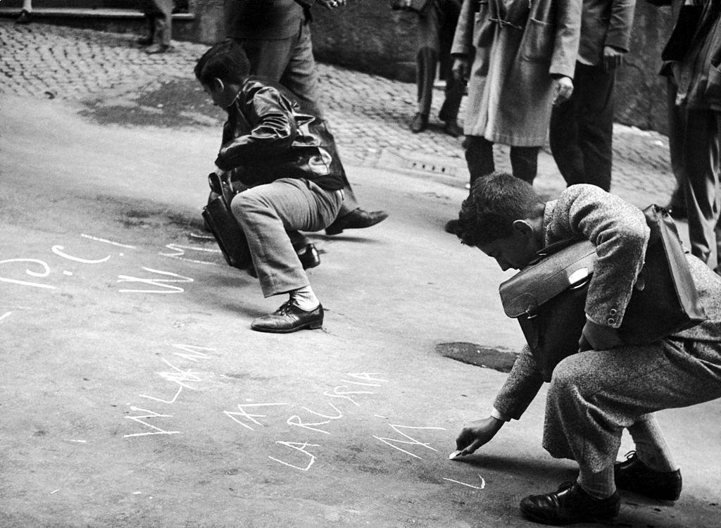 Students writing on the ground some solidarity messages to the rebels in Hunary after the repression by Soviet Tanks, 1956.