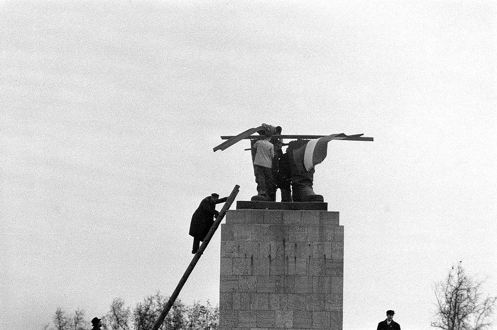 Protestors putting Hungarian flag in what remained of Stalin's boots, and the head fell to the ground in Gyor, Hungary on October 23, 1956