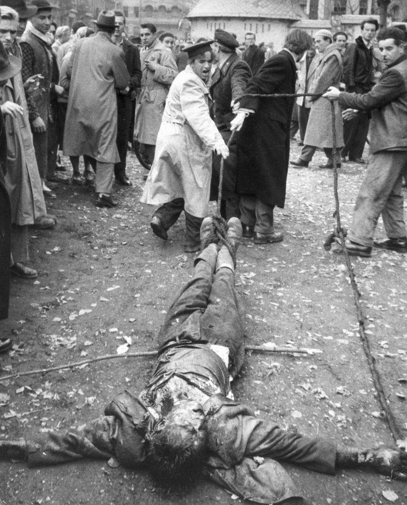 A beaten Hungarian colonel in the AVO, the secret police of the communist regime, is dragged along the ground by ropes attached to his ankles by angry protesters.