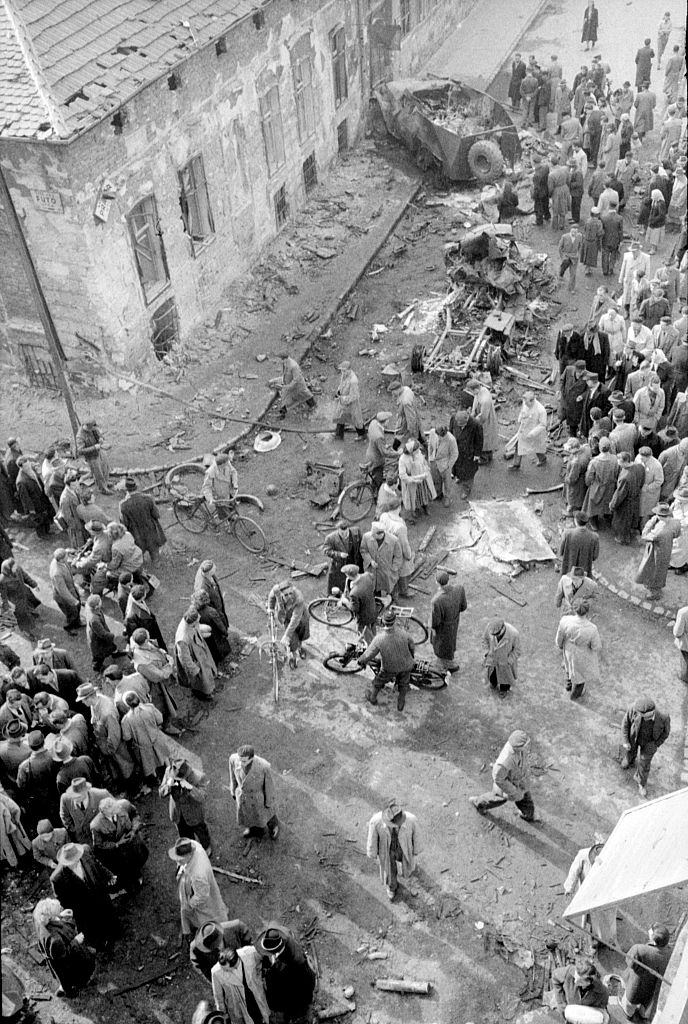 The crowd looking at the ruins after the uprising that took place in the streets of the city.