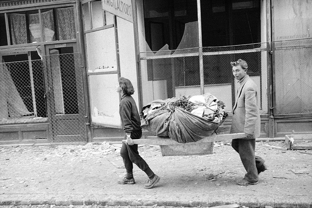 Two people carrying their things across the ruins of the city. Budapest, 29th October 1956.