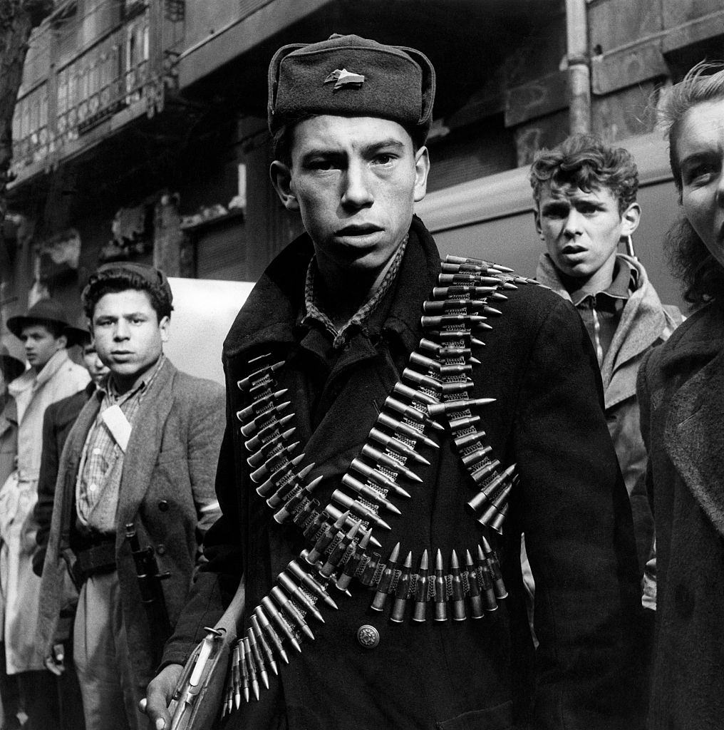 A young rebel with two cartridge belts loaded with bullets taking part in the Hungarian Revolution of 1956.