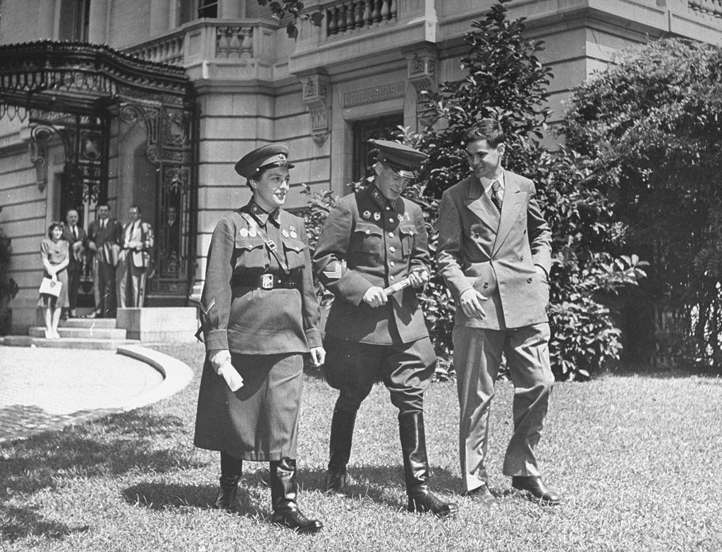 Lyudmila Pavlichenko walking across the lawn in front of the Russian Embassy with two gentlemen, 1942.