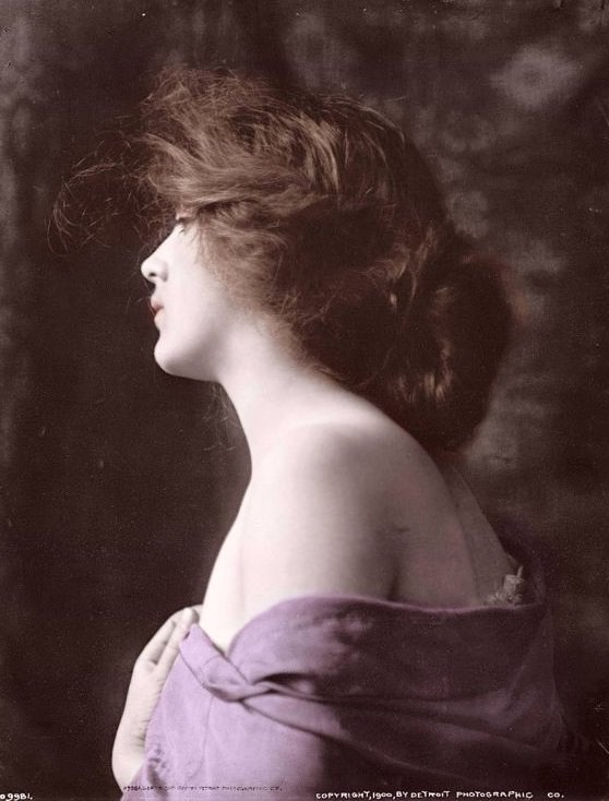 Woman model in profile with hand at bosom