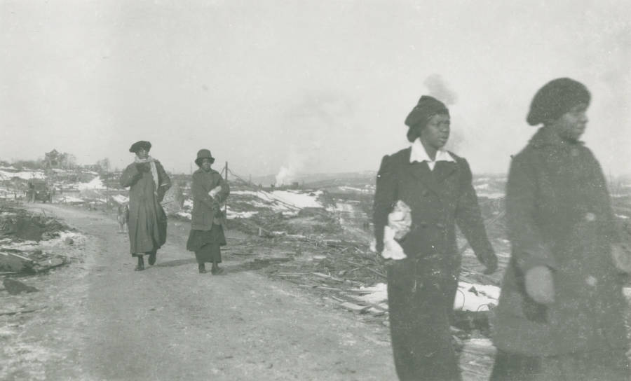 Women from Africville, the black district of Halifax, make their way through the rubble.