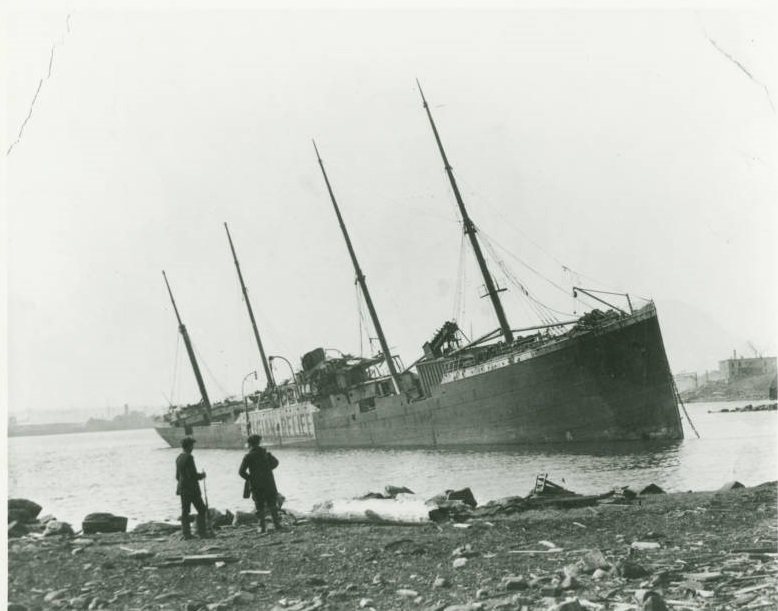 The ruined heap of the SS Imo, one of the ships that caused the explosion, lies lifelessly in the water.