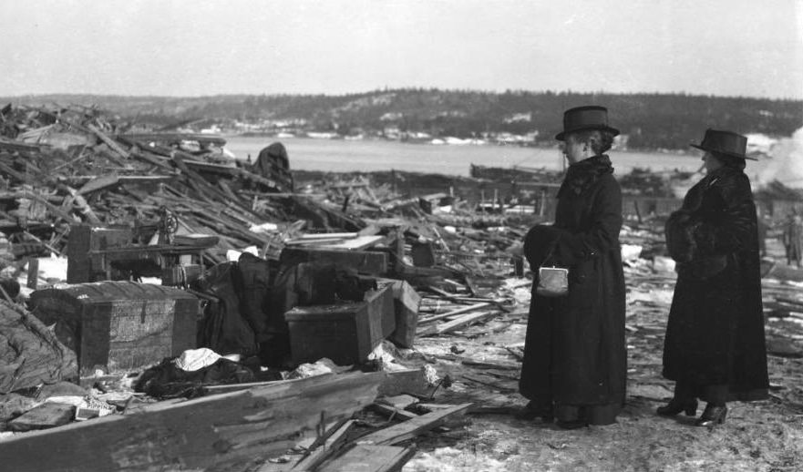 Two women look at the debris, hoping something of the life that went up in flames can still be recovered.