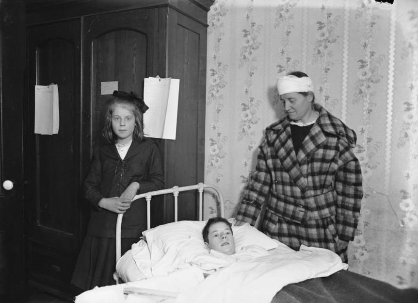 A family stands vigil over their wounded child's bed.