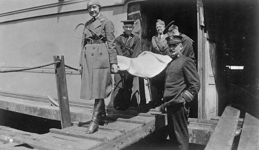 American Red Cross workers help carry a wounded man to a makeshift hospital set up nearby.