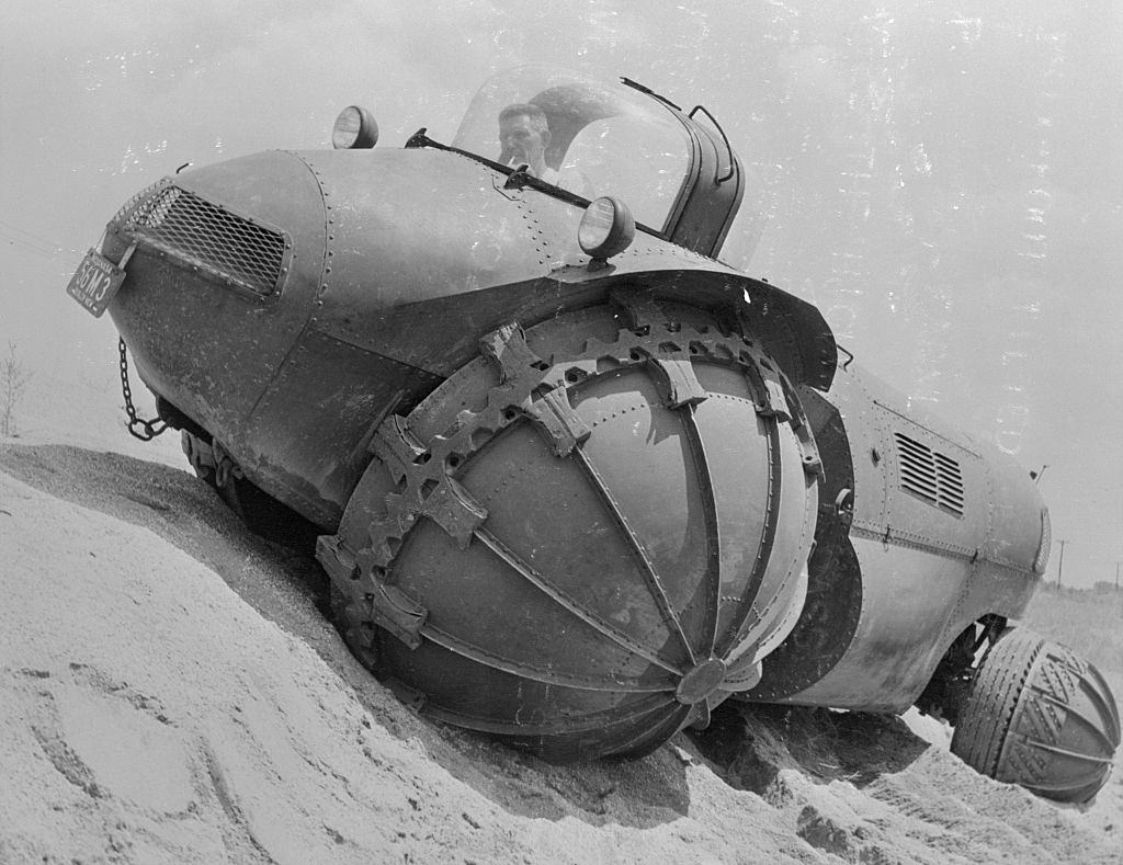 It rolls on six foot tilted hemispheroidal wheels over sand, swamps, snow, farmland and other cross country areas.