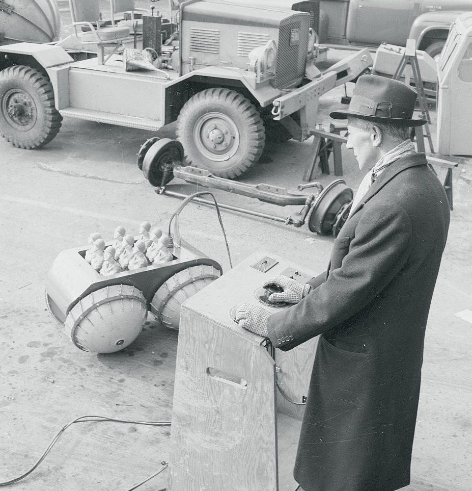 Elie P. Aghnides, demonstrating his invention 'Baby Rihno' at Marmon-Herrington Co. Inc.