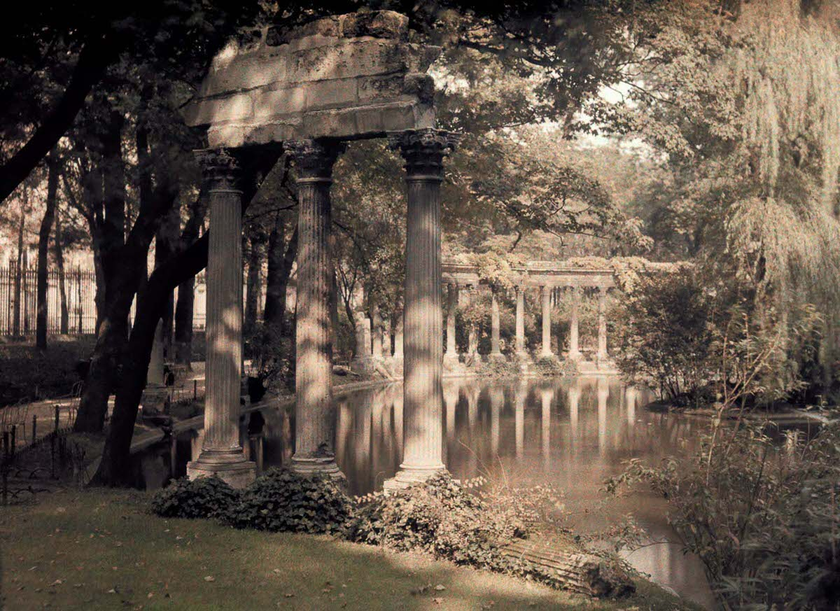 A colonnade and lake in a garden.