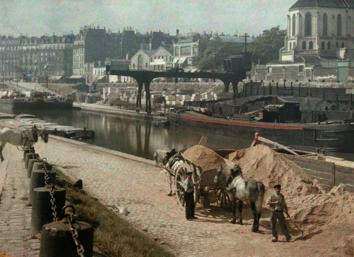 Horses and workers on a riverbank.
