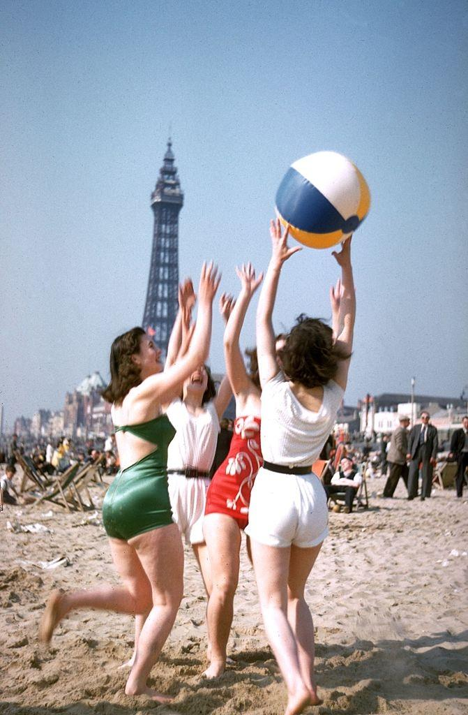 A group of young women play with a beach ball on Blackpool beach, 1955.