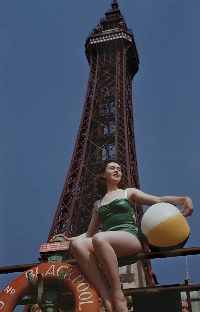 A young woman with a beach ball in front of Blackpool Tower in Blackpool, Lancashire, UK, 23rd June 1955.