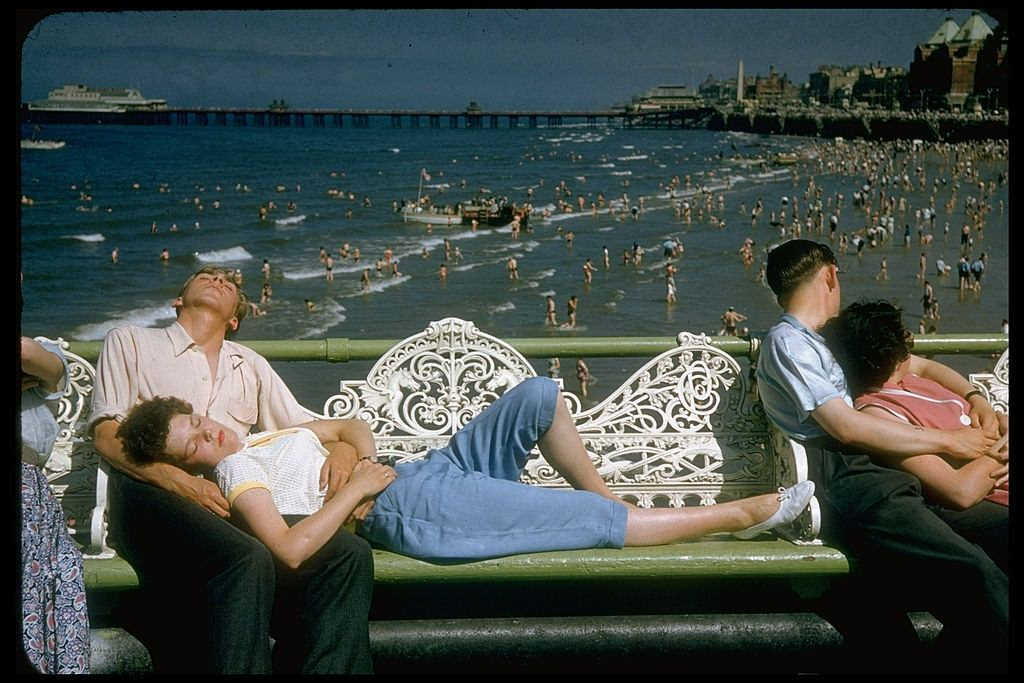 Young woman lying on white wrought iron bench w. head resting in lap of boyfriend in Blackpool beach, 1955.