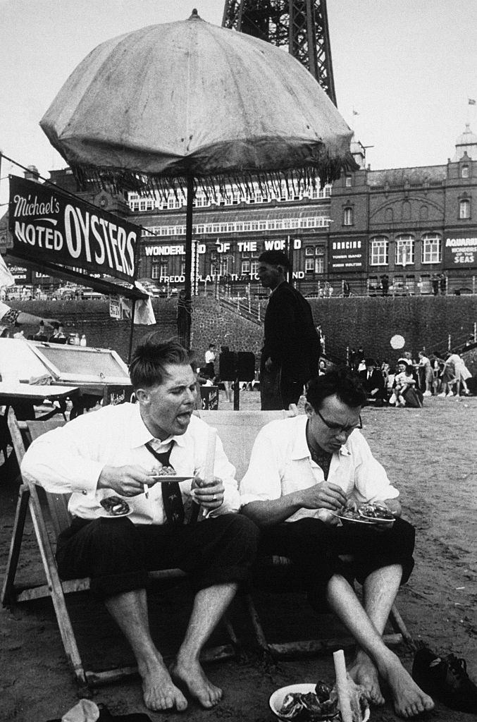 The comedians Eric Morecambe and Ernie Wise, enjoying some of the local delicacies on the beach at the foot of the Blackpool Tower, 1953.