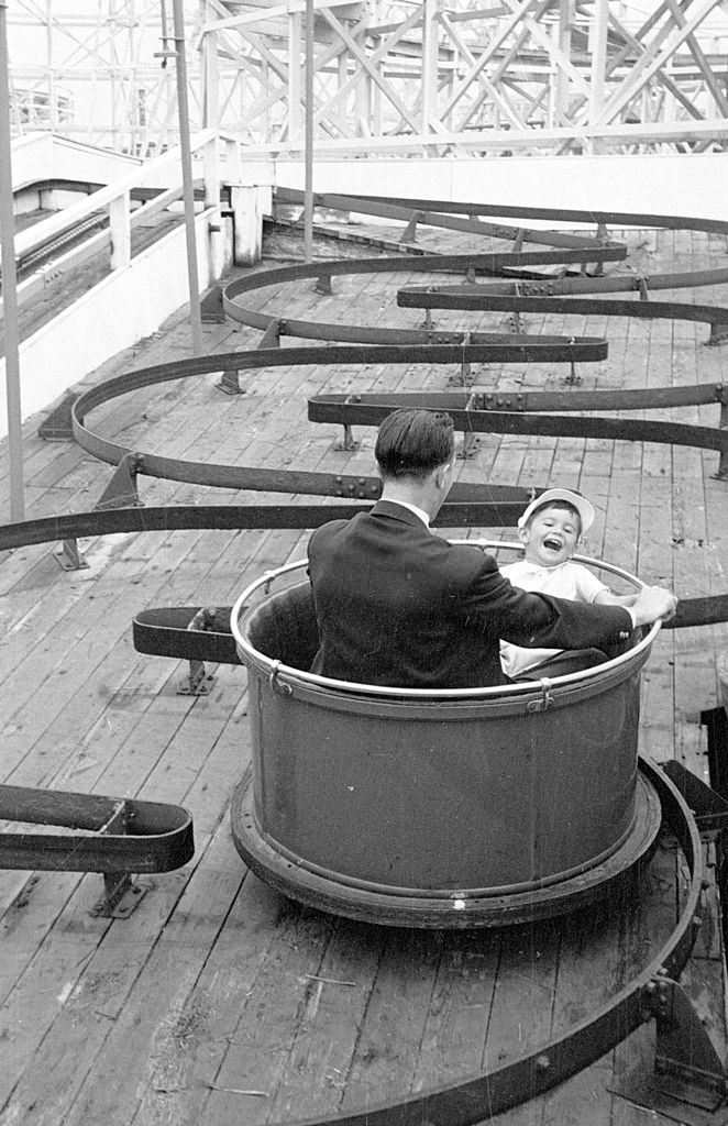 A father and son enjoying a fairground ride on the pleasure beach at Blackpool, 1953.