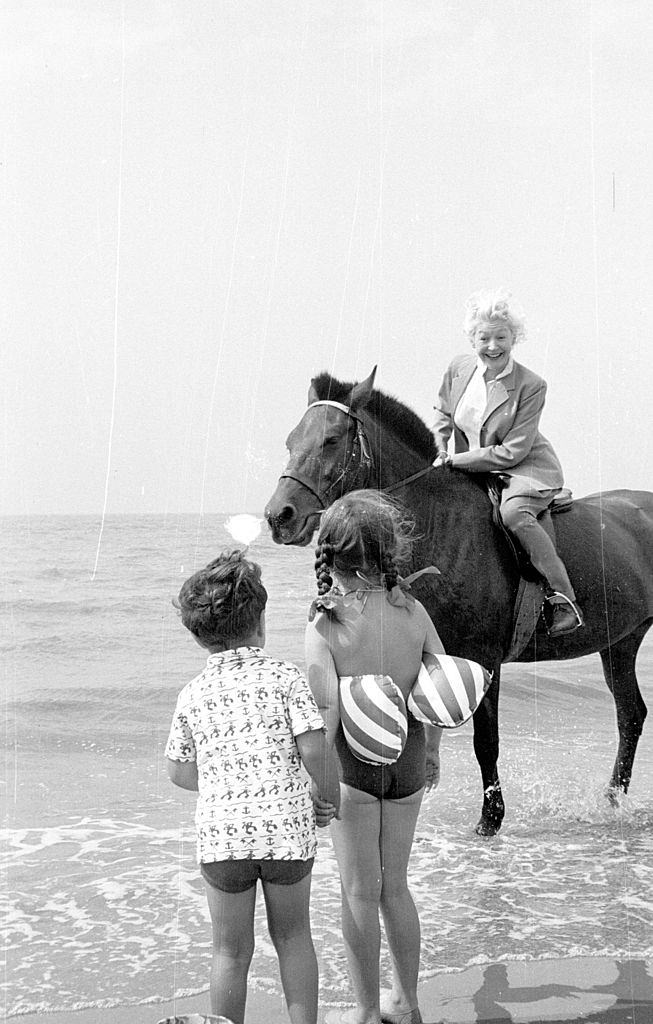 Marianne Lincoln, who will compere the 'Stars At Blackpool' television show, enjoying a horse ride on the beach where she meets two young fans, 1953.