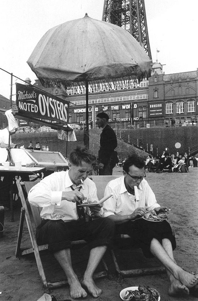 British comedy double act Eric Morecambe  and Ernie Wise, in rolled up tousers, eating seafood on the beach at Blackpool, 1953.
