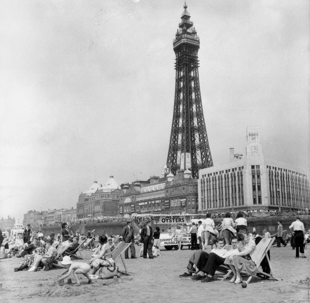 Blackpool Tower behind holidaymakers relaxing on the beach of the famous Lancashire resort, 1953.