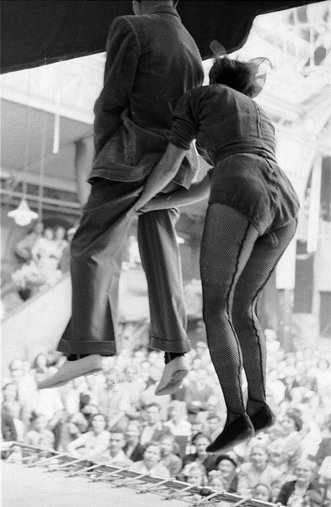A member of the audience, held by the seat of his pants by a performer, jumps up and down on a trampoline in front of the crowd at the famous seaside resort of Blackpool, 1953.