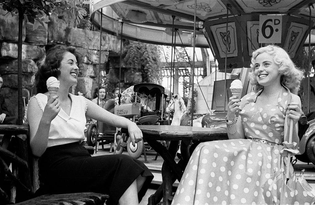Tourists enjoy icecreams at the fairground in the seaside resort of Blackpool, 1953.