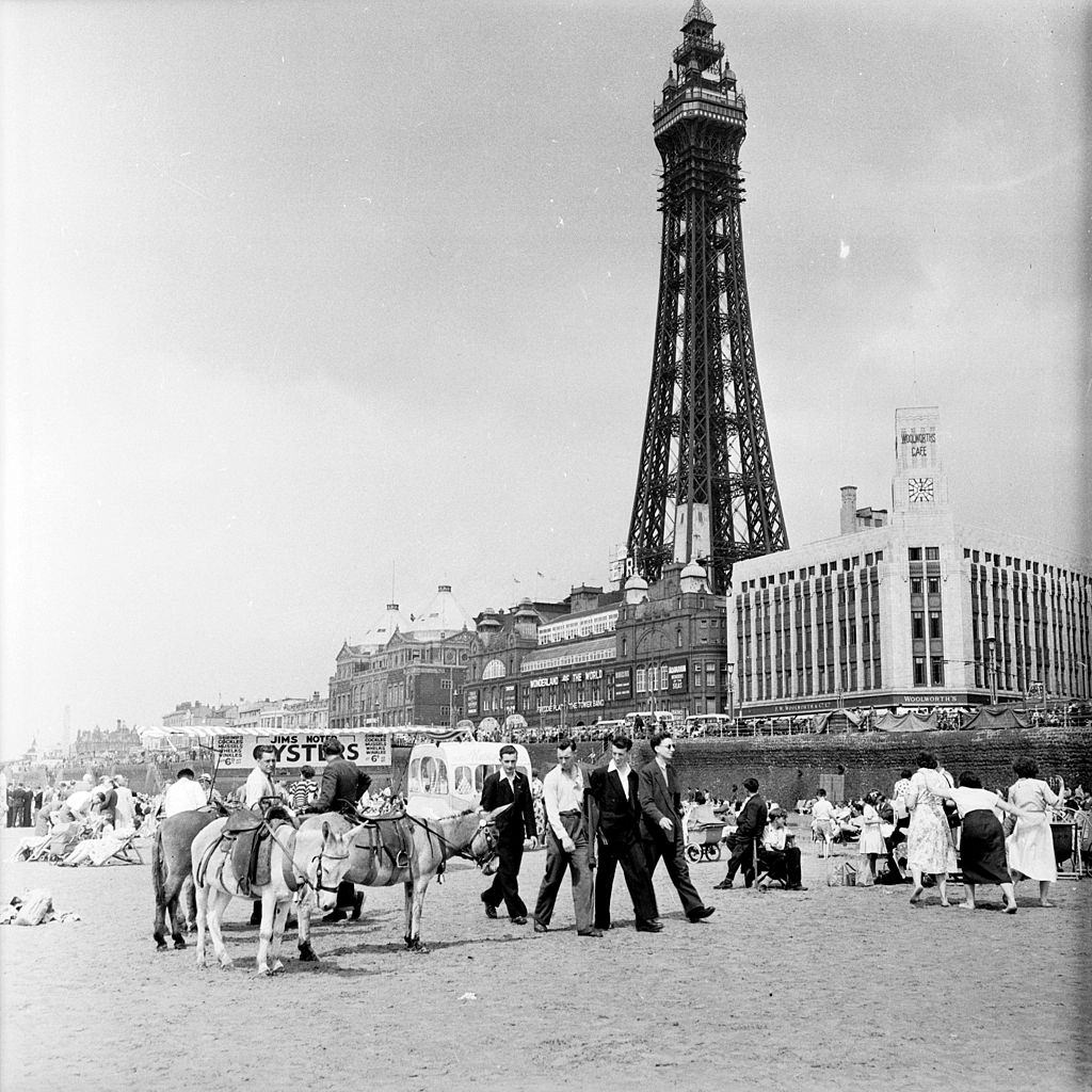 Tourists on the beach at Blackpool with the Blackpool Tower behind them, 1953.
