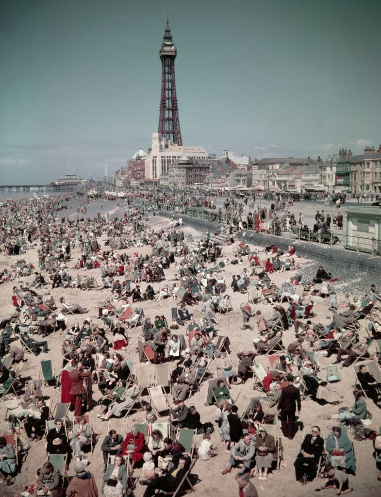 Holidaymakers and visitors, many seated in deck chairs, enjoy a day on the beach at the seaside resort of Blackpool in Lancashire in August 1952.