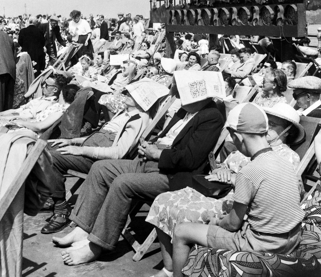 Two gentleman sitting on a busy Blackpool promenade in Lancashire, wearing newspapers on their heads as improvised sun hats, 26th July 1952.