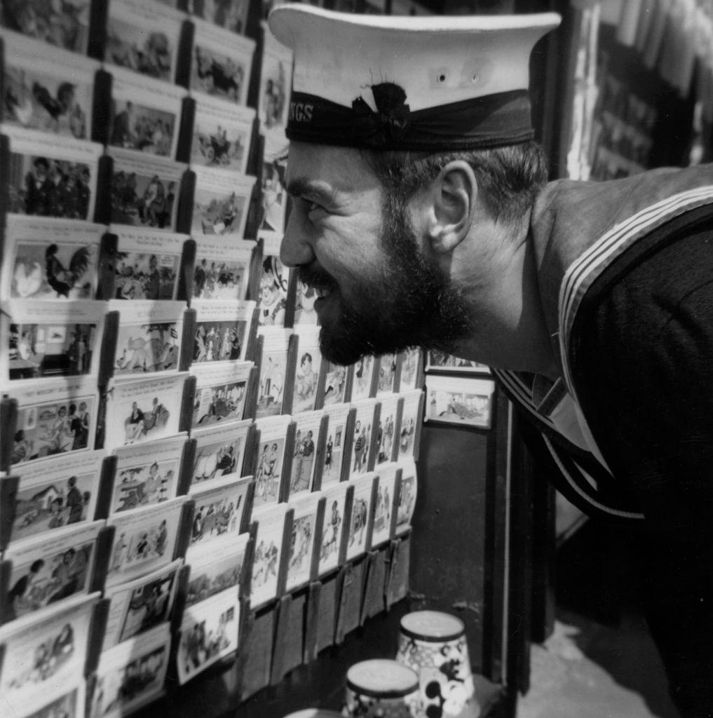 A sailor looking at a selection of postcards at the seaside in Blackpool, 1951.