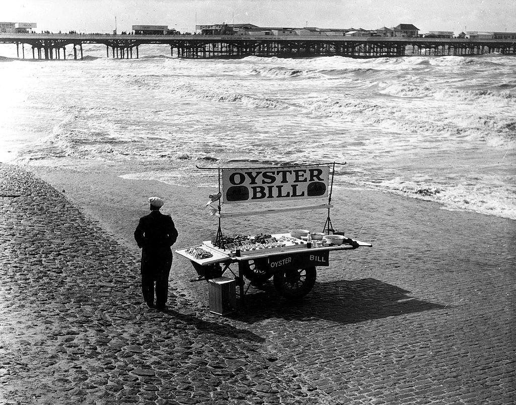 """A man standing with a barrow displaying """"Oyster Bill"""" on the sand at Blackpool, 1951."""