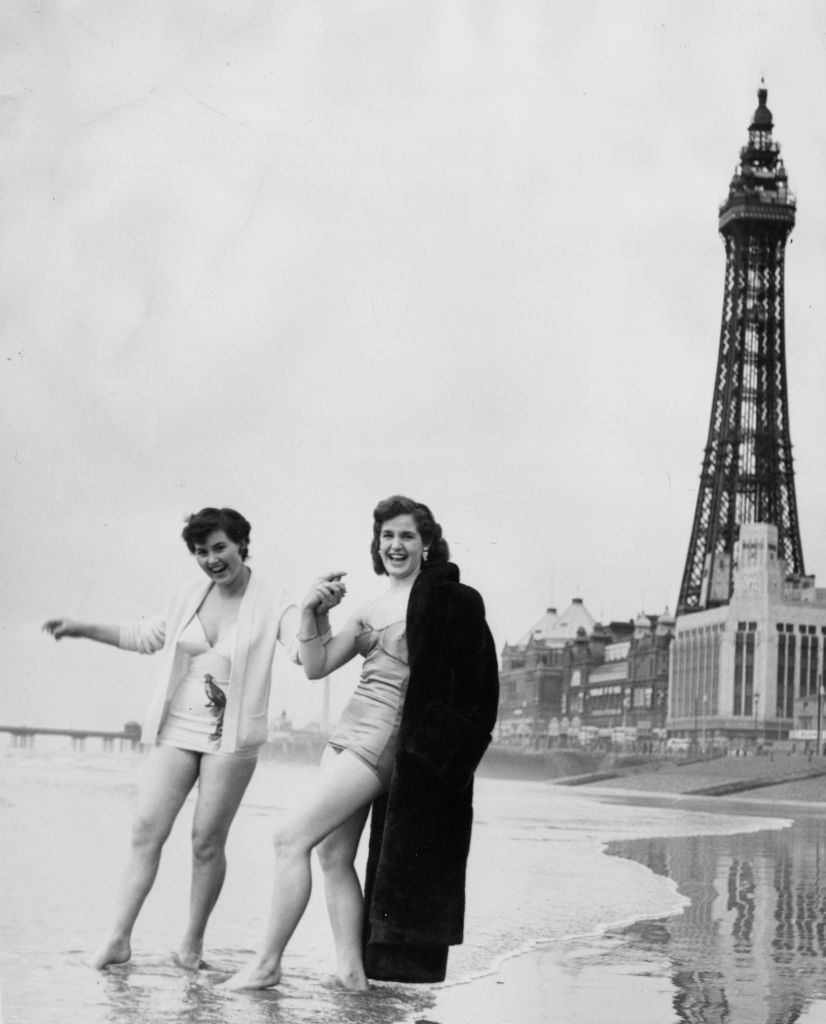 Two young women from Blackpool tentatively paddling at the water's edge, 1954.