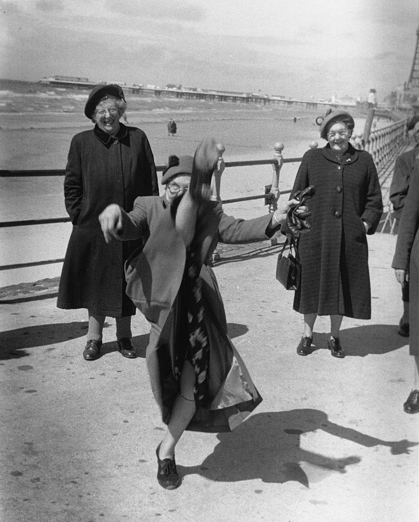 An elderly women performs a high kick on the promenade at Blackpool, 1955