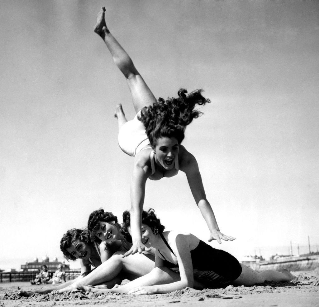 Dancing teacher, Hazel Cleaver, leaps over her friends as they enjoy the summer sunshine on the beach, 1955.