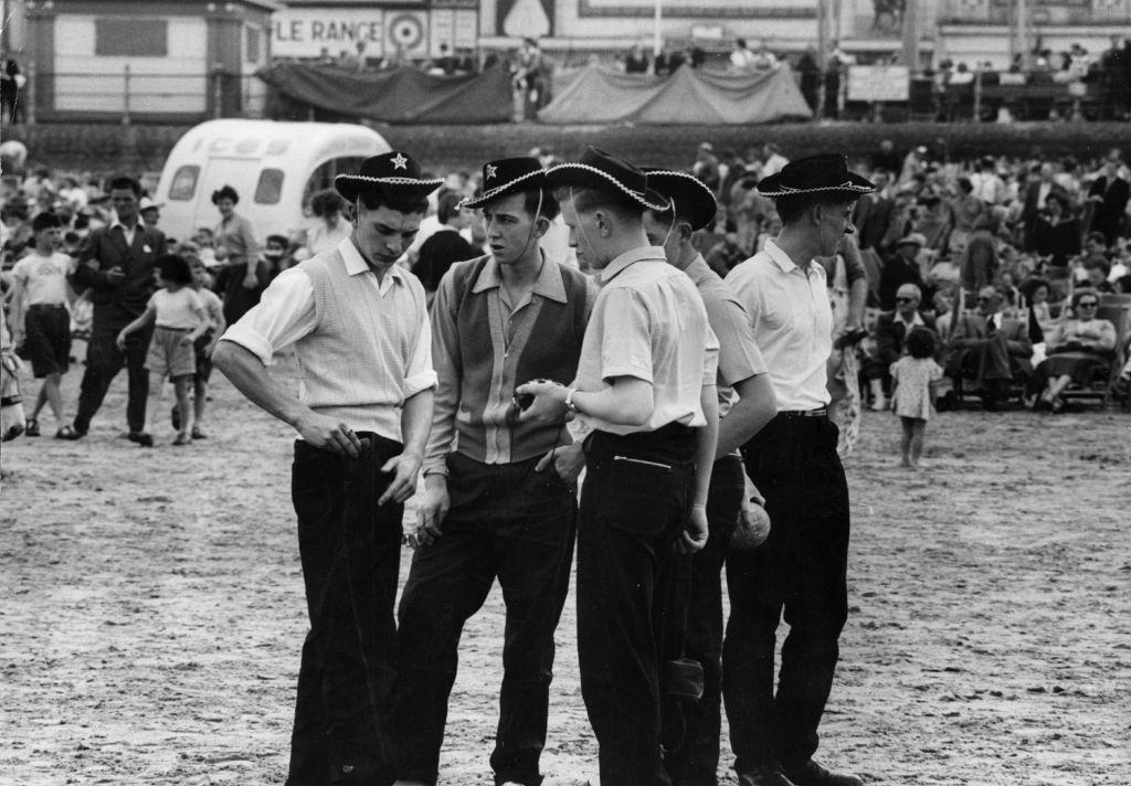 A group of teenagers in cowboy hats on the beach at Blackpool, 1956.