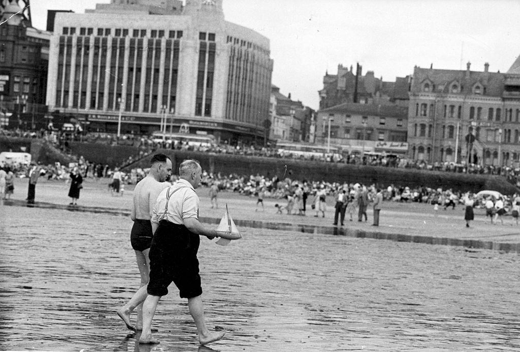 Two men with their toy boat on the beach at Blackpool, July 1956.