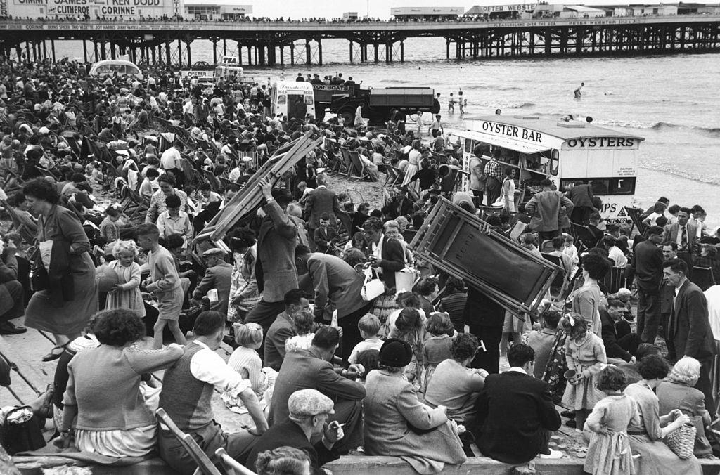 A crowd of people on the beach at Blackpool, some carrying deckchairs, July 1956.