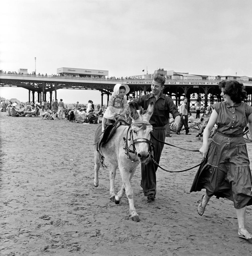 A young holiday makers having a Donkey ride on the beach at Blackpool, Lancashire, 18th July 1957.