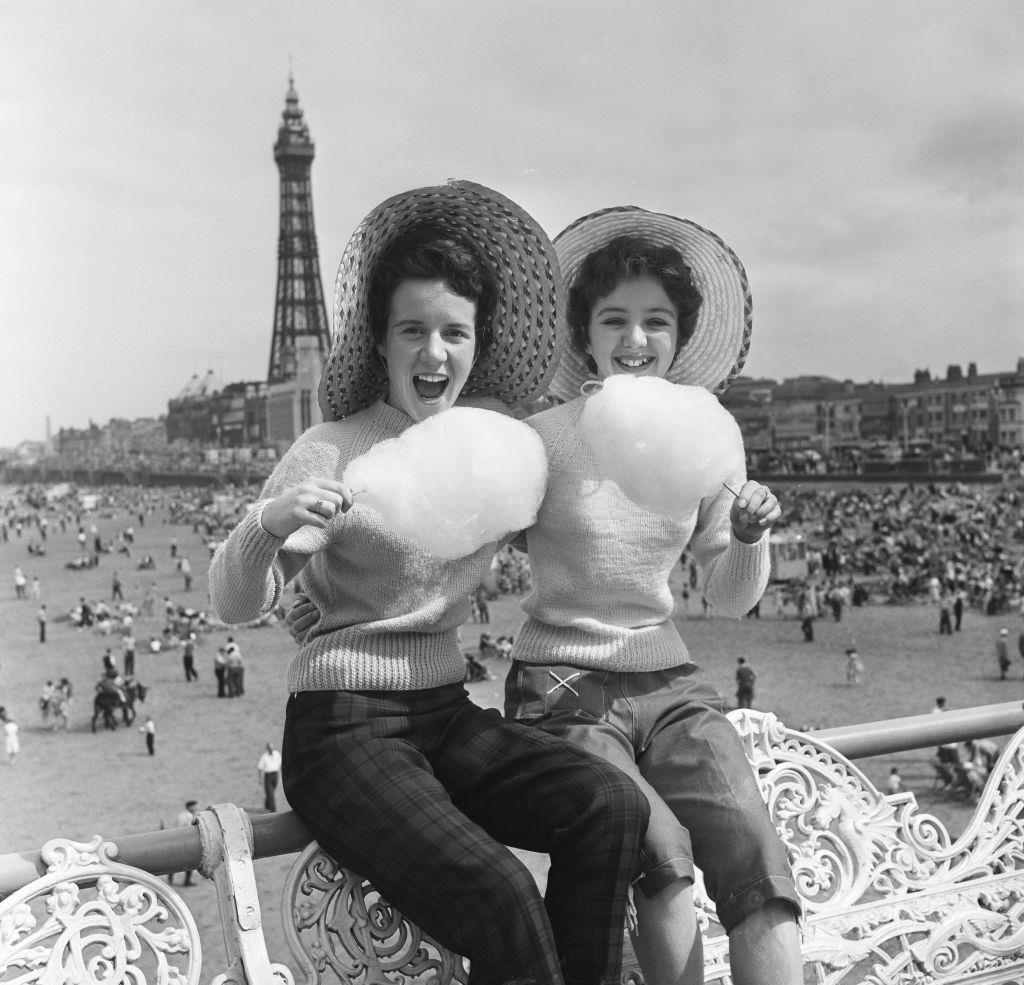 Jean Clark and Mary Cuppler enjoy eating candy floss on the pier at Blackpool, 1957.