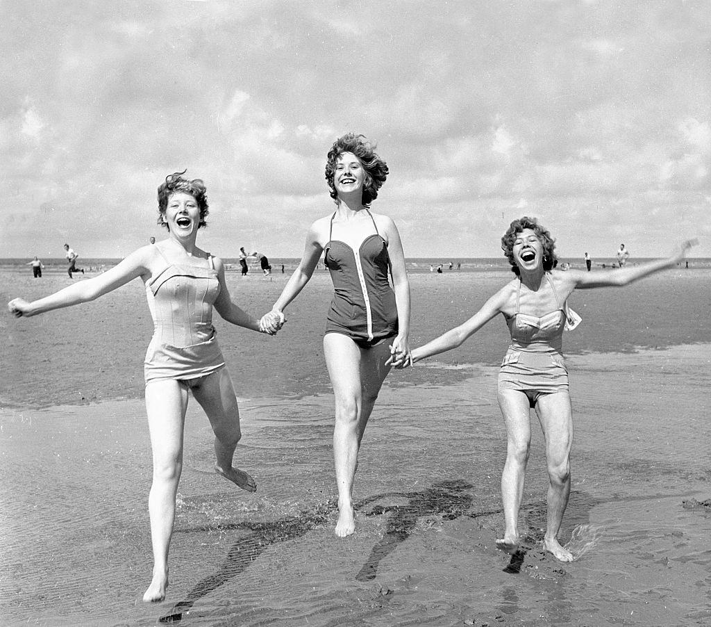Three girls holding hands on the beach at blackpool August 1958