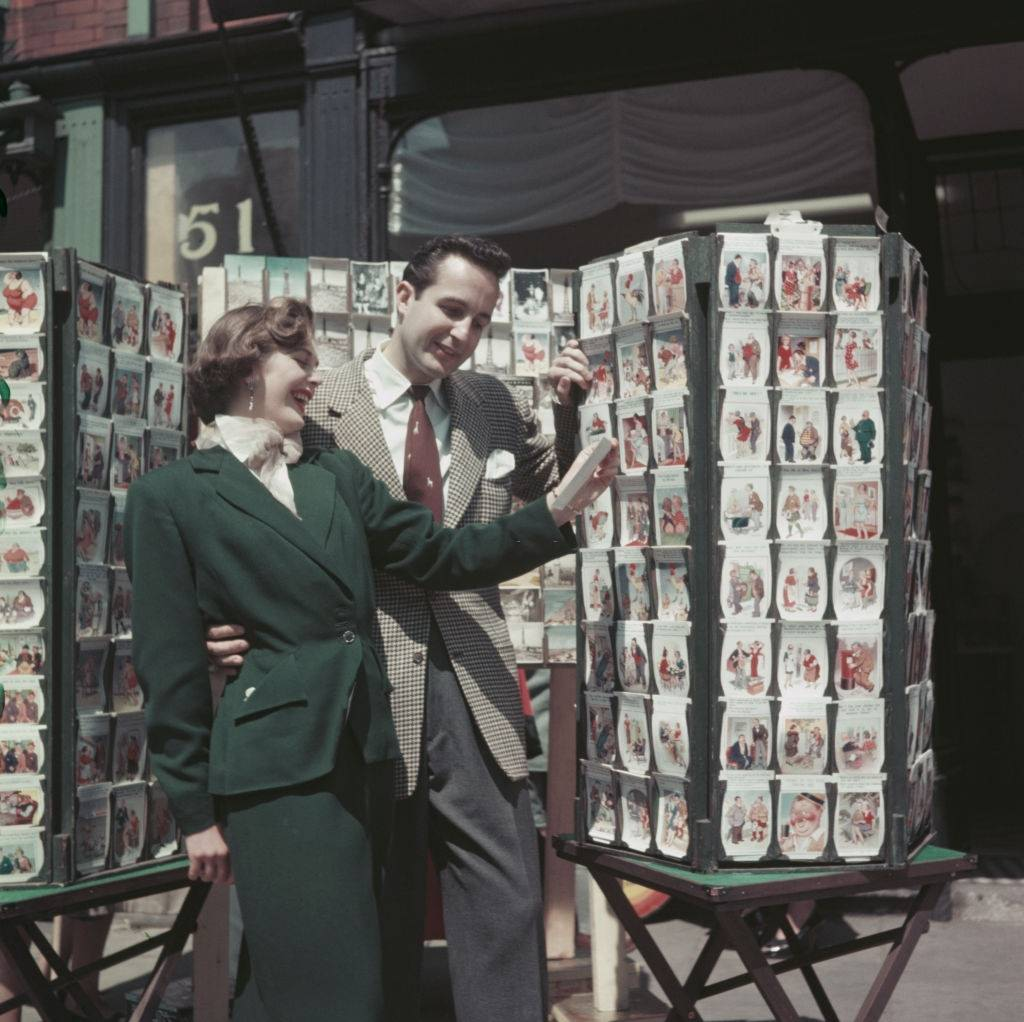 A young couple laugh as they view a carousel of saucy postcards at a postcard shop in the seaside resort of Blackpool, Lancashire in July 1954.