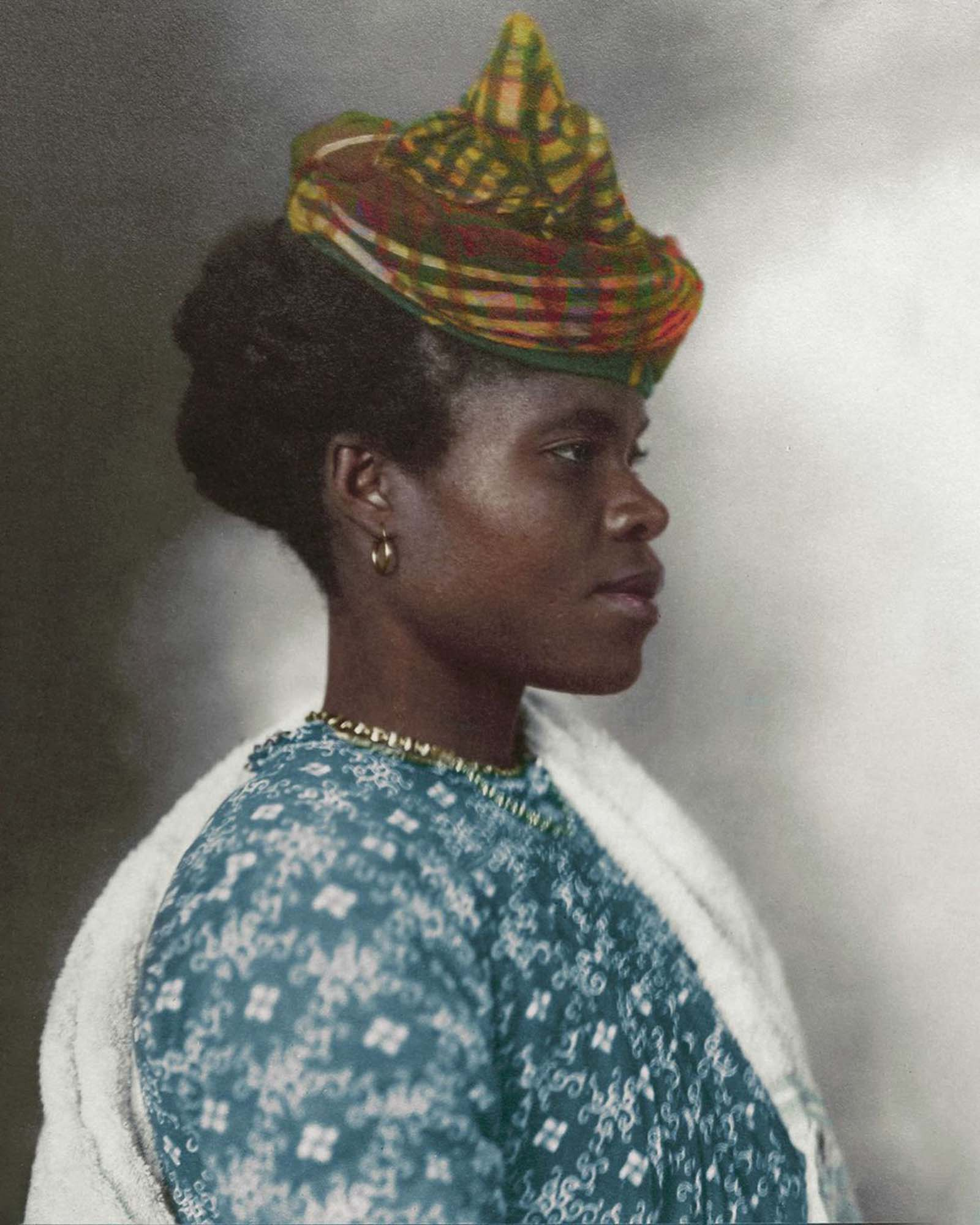 """Guadeloupean Woman."""" The elaborate tartan headpiece worn by this Guadeloupean woman can be traced back to the Middle Ages, where the eastern Indian city of Madras was famed for its cotton making. First plain, then striped and then with increasingly elaborate patterns, the Madras fabric that was expo"""