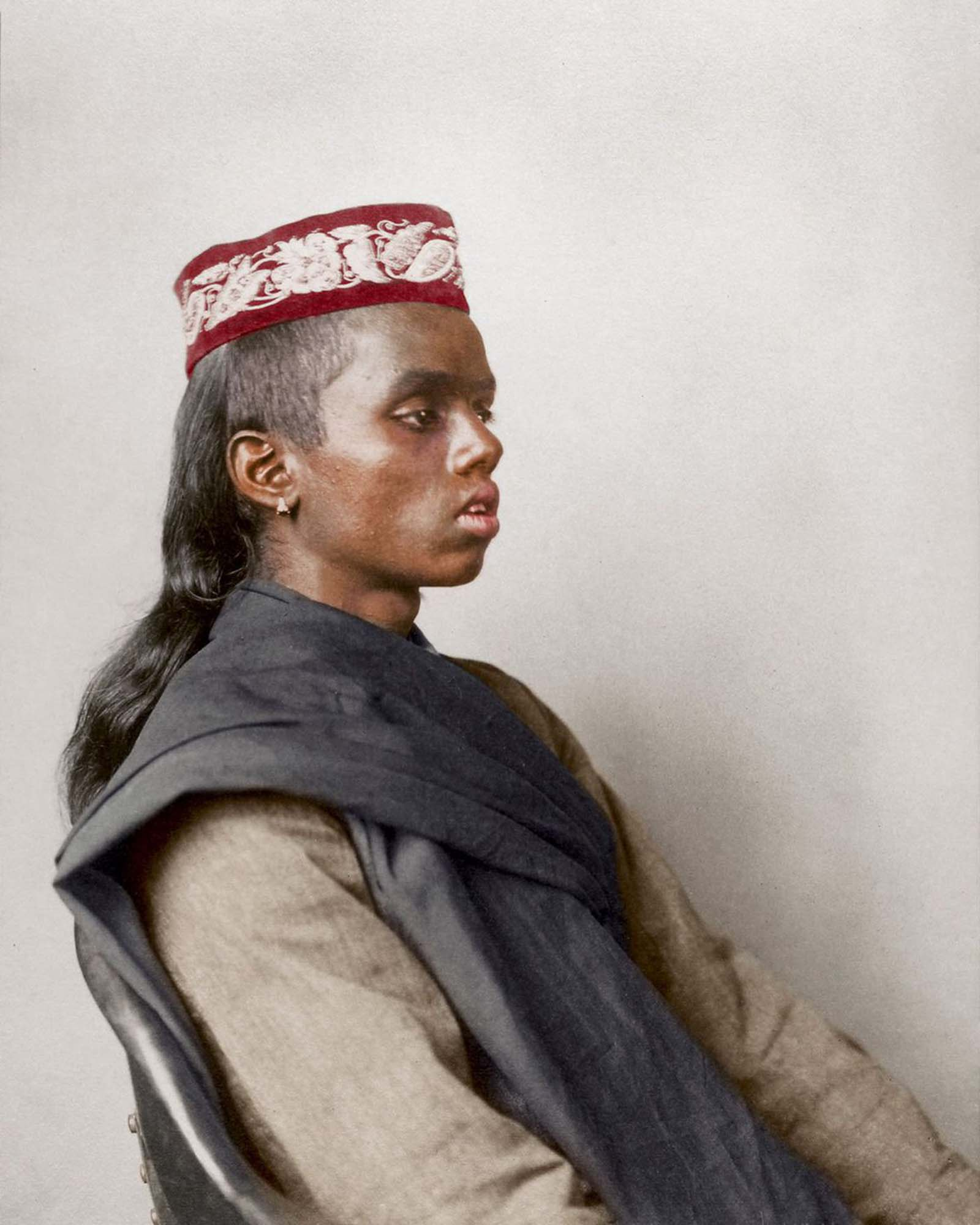 """Hindoo boy."""" The topi (a word to denote """"cap"""") is worn all over the Indian subcontinent with many regional variations and cultural significance, and is especially popular in Muslim communities, where it is known as a taqiyah. Both the cotton khadi and the prayer shawl are most likely handspun on a c"""