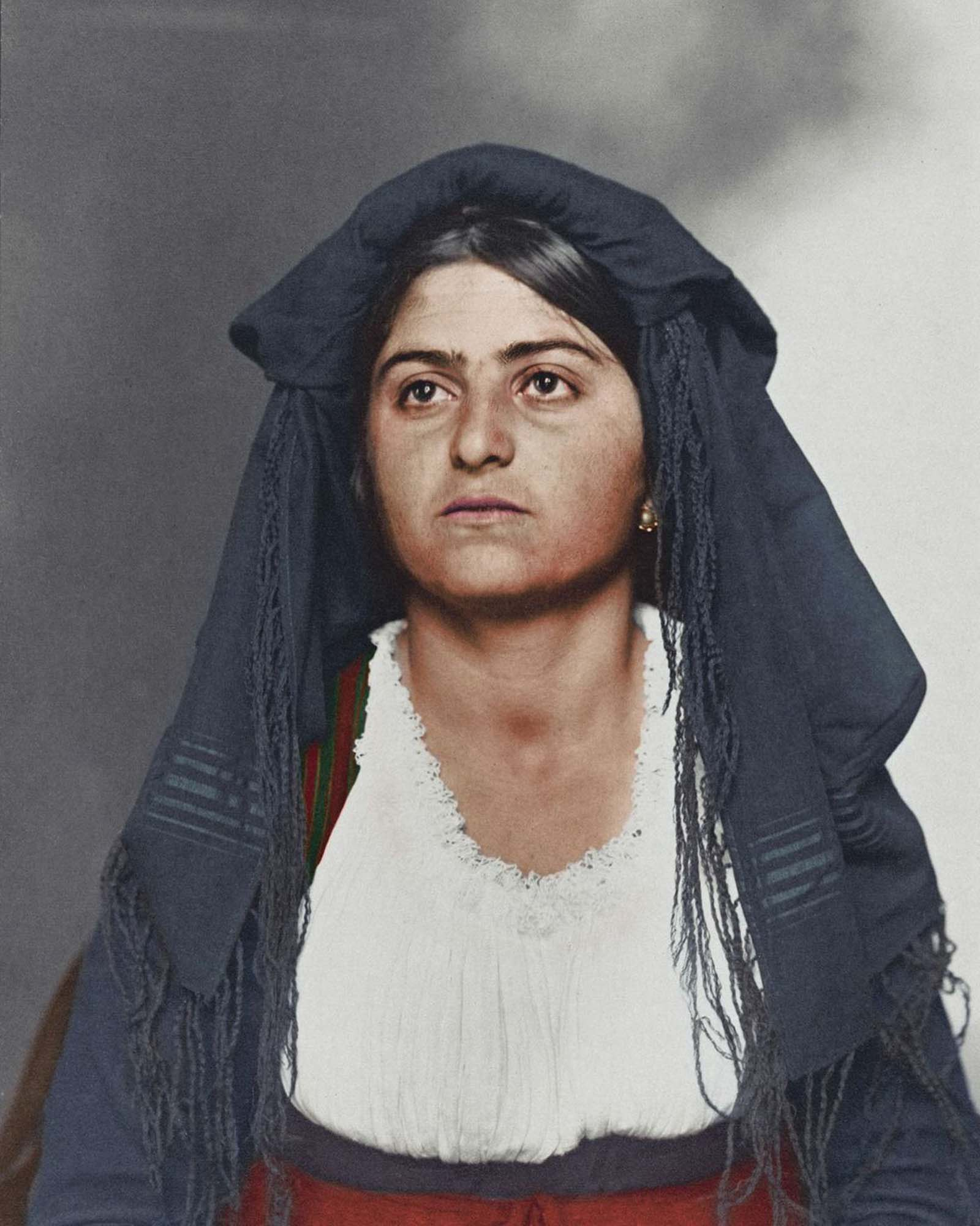 """Italian woman."""" This traditional dress was most likely homespun and consisted of a long, wide dress to cover the ankles. Above, a bodice and sleeves were tied in such a way to expose portions of the linen blouse. Colors and materials were usually regional. Shawls and veils were also a common feature"""